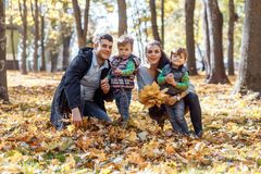 Natural pictures of a happy family of four having fun outsiade on a sunny autumn day. Togetherness and happiness concept stock photo