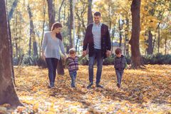 Natural pictures of a happy family of four having fun outsiade on a sunny autumn day. Togetherness and happiness concept stock photos