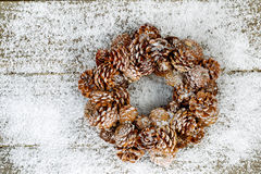 Natural Pine Cone Wreath on Snow and wood. Natural pine cone wreath on snow and rustic wood setting the holiday mood Royalty Free Stock Image