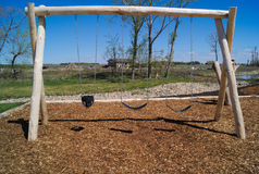 Natural Playground Swing Set Wood structure. A natural playground swing set made of wood with mulch underneath it Royalty Free Stock Images