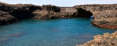 Natural Pool and Arch. Baia - A natural bay formed by volcanic lava from past eruptions with natural arch surrounded by the blue waters of the Atlantic creating Stock Photo
