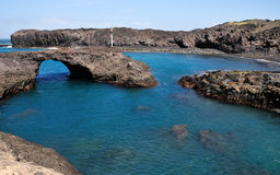 Natural Pool and Arch in Baia. Baia a natural oasis made of a volcanic arch over a clear blue water lagoon serves as one of the natural wonders of the the island Stock Photography