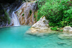 Natural pool with azure water and a small waterfall. Natural pool with crystal clear water and a small waterfall Stock Photography