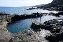 Natural pool on volcanic rocks shore stock images