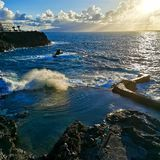 Natural pool and waves splashing while the sun is setting in Los Gigantes, Tenerife, Spain. Natural pool waves splashing sun setting los gigantes tenerife spain stock photo