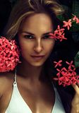 Natural portrait of beautiful sexy blond young woman model with perfect clean skin near summer flowers in tropical island Royalty Free Stock Photography