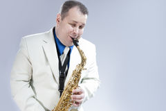 Natural Portrait of Expressive Male Saxophone Musician Performing in White Suit Stock Photos