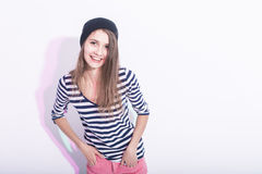 Natural Portrait of Happy Laughing Caucasian Brunette Girl in Hat. And Striped Shirt. Posing Against White Background.Horizontal Image Stock Image