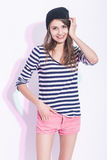 Natural Portrait of Happy Laughing Caucasian Brunette Girl in Hat. And Striped Shirt. Posing Against White Background. Vertical Shot Stock Photography
