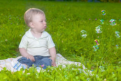 Natural Portrait of Little Cute Caucasian Toddler Child Sitting on Grass Outdoors Stock Photo