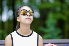 Natural Portrait of Tranquil African American Teenager With Long Dreadlocks Posing in Park Outdoors in Sunglasses. Stock Images