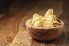 Natural potato chips with black pepper in wood bowl on table with copy space stock image