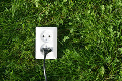 Natural power. An electrical cord connected to an electrical socket that generates power from green grass or other relevant natural sources of energy stock photography
