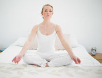 Natural pretty blonde meditating on bed Stock Image