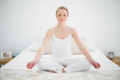 Natural pretty blonde meditating on bed with closed eyes Stock Photos