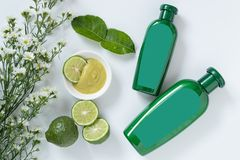 Natural products for hair concept. two size of green plastic bottle with blank label contain herbal bergamot shampoo. Decorate with slide kaffir limes ,kaffir stock photo