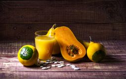 Natural pumpkin juice. Still life with pumpkin and pumpkin juice on a wooden table Stock Images