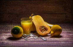 Natural pumpkin juice. Still life with pumpkin and pumpkin juice on a wooden table Stock Photography