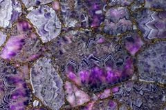 Natural purple amethyst backlit, the light highlights how translucent parts of the stone and it becomes pink. Beautiful texture stock image