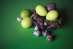 Easter eggs in the nest on green paper background stock photo