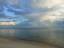 Natural rainbow and clouds. Evening seascape - rainbow, blue and white clouds over the calm sea royalty free stock image
