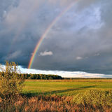 Natural rainbow over autumn field and dark sky. Royalty Free Stock Images