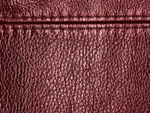 Natural red leather texture background with seam. Genuine material Royalty Free Stock Photography