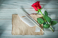 Natural red rose vintage paper sheet feather on wooden board cel Stock Photos