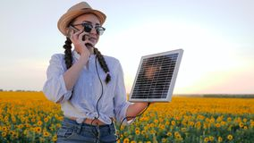 Natural resources, woman in backlit talk mobile and keep solar battery tracking sun to charge battery, girl speaks by stock video