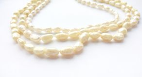 Natural river pearl beads on a gentle pearl necklace on a white background stock photo