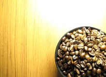 Natural Roasted Coffee beans  in black bowl. On wooden table Royalty Free Stock Photos