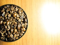 Natural Roasted Coffee beans  in black bowl. On wooden table Royalty Free Stock Image