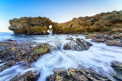 Natural rock arch, cliff and beach. Stock Photography