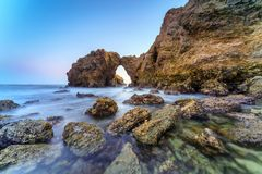 Natural rock arch, cliff and beach. Stock Photo