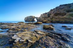 Natural rock arch, cliff and beach. Royalty Free Stock Image
