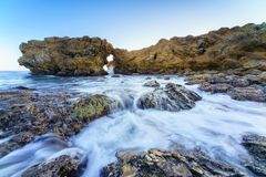 Natural rock arch, cliff and beach. Royalty Free Stock Images