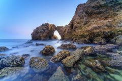 Natural rock arch, cliff and beach. Stock Photos