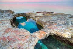 Natural rock bridges over crystal clear water. Natural rock bridges over crystal clear blue water on an offshore reef in a tranquil ocean at sunset with a royalty free stock photography
