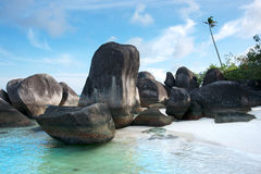 Natural rock formation on the blue turquoise colored seashore and white sand beach. Stock Photo