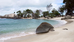 Natural rock formation on blue turquoise colored seashore and white sand beach with plants and trees at the background in Belitung Stock Images
