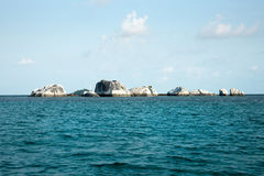 Natural rock formation in sea at Belitung Island. Natural rock formation in sea at Belitung Island in the afternoon and white lighthouse at the background Royalty Free Stock Images