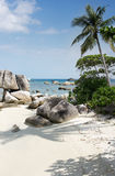 Natural rock formation in the sea and on a white sand beach with a palm tree in Belitung Island. Natural rock formation in the sea and on a white sand beach Stock Images