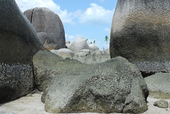 Natural rock formation on a white sand beach and green palm trees at the background in Belitung Island. Stock Photos