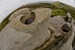 A natural rocks formation with a view of the green fields of the distant landscape in the Peak District,Derbyshire E Royalty Free Stock Photos