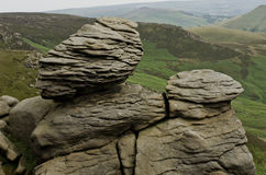 A natural rocks formation with a view of the green fields of the distant landscape in the Peak District National Park Derbyshire E Royalty Free Stock Photo