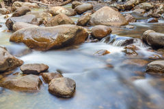 Natural rocks over the flowing clear water. Stock Photography