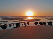 Natural rocks in the water from the atlantic ocean at sunset Stock Image