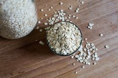 Natural rolled oats piled in bowl and in storage jar stock photography