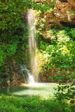 Natural, romantic sunlit waterfall falling into a small pond Stock Photography