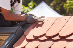 Natural roof tile instaalation. Roofer builder worker use ruller to measure the distance between the tiles. Natural roof tile instaalation. Roofer builder Royalty Free Stock Images